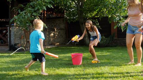 4k video of happy elder sister having water battle on toy guns with her little Archivo