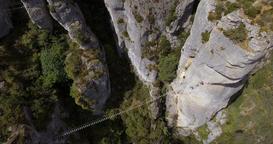 Rope Bridge Across Steep Rock Formations Aerial Overhead Footage