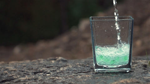 glass of fresh water with waterfall in the background Stock Video Footage