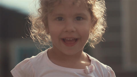Portrait of the little pretty girl with long hair waving her hand in gront of Footage