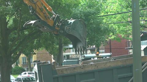 Excavator scoops and dumps debris into truck Footage