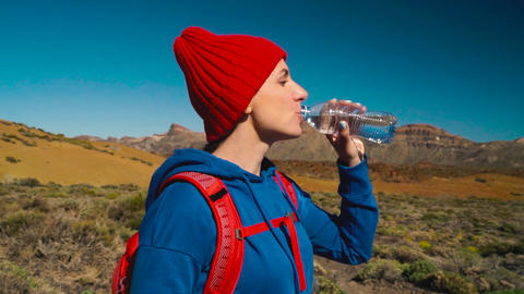 Hiking woman drinking water after hike on Teide, Tenerife. Caucasian female Live Action