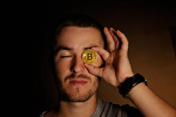 Young Beard Man Look Through Golden Bitcoin Currency On Brown Background フォト
