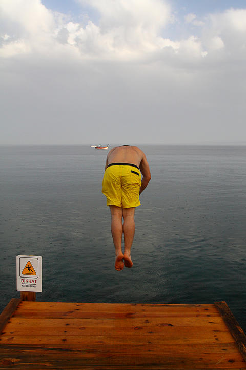 Young Man Jumping Into The Sea Photo