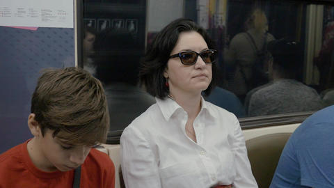 Mother and son ride the train on the subway, in the evening. Son wants to sleep GIF