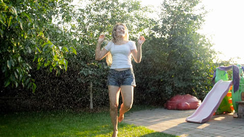 Slow motion video of happy young woman dancing and jumpin gunder water splashing Live Action