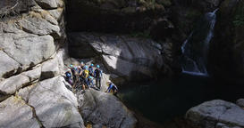 Adventure Seeking Rock Climbers Swim Across a Waterfall's Plunge Pool Footage