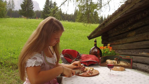 teenage girl dressed in typical Tyrolean dress cuts some slices of bacon GIF