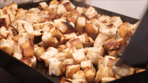 Frying bread cubes on a griddle with olive oil Live Action