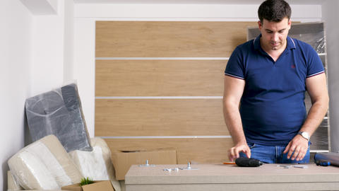 Man is assembling furniture in new house Stock Video Footage