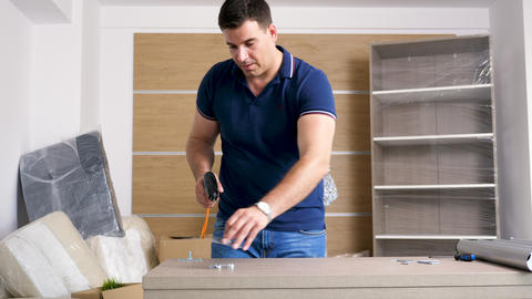 Man is assembling furniture in new house Footage