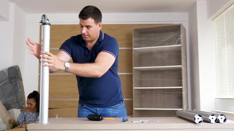 Husband assembling furniture in new house GIF
