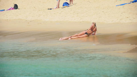Two girls sunbathing on the beach in Karon Footage
