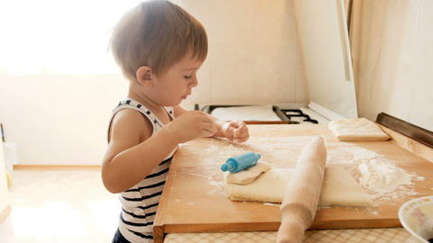 4k footage of adorable toddler boy playing with dough while making pie on Footage