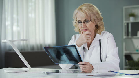 Concerned female pulmonologist examining X-ray of patient's lungs, diagnostics Live Action
