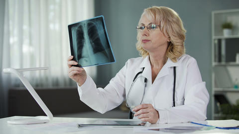 Doctor examining X-ray of patient's lungs making notes in medical records Live Action