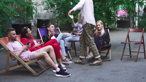 Company of young people is resting on a summer area in a cafe Footage