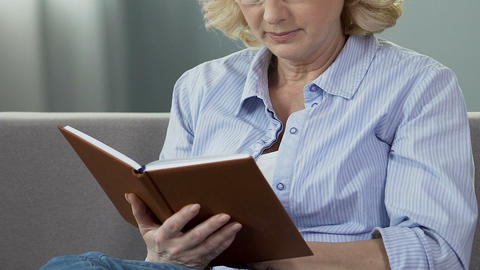 Retired woman sitting on couch and reading book, avid book reader, leisure time Live Action