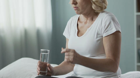 Retired woman taking pill, drinking it up with water, health troubles medication Live Action