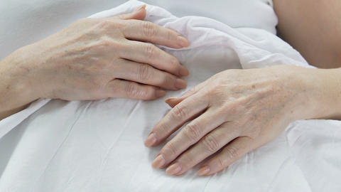 Hands of elderly woman lying in bed, wrinkled skin, aging person, experience Footage