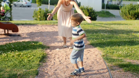 4k video of cute laughing toddler boy running in park towards and away from Footage