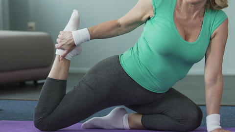 Senior woman sitting on fitness mat, stretching her leg, yoga pose, flexibility Live Action