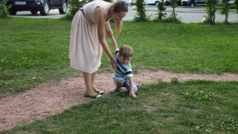 4k footage of young mother in skirt running and chasing her laughing toddler boy Footage