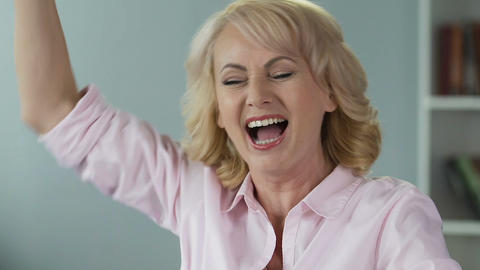 Joyful middle-aged woman rejoicing lottery prize, screaming and laughing Footage