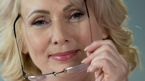 Good-looking mature woman wearing eyeglasses and smiling, ophthalmology Footage