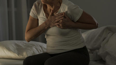 Heart attack, aged female sitting on sofa and touching chest, health problem Live Action