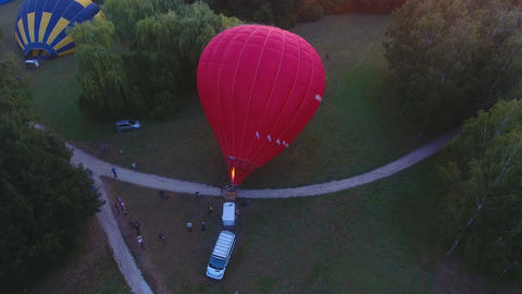 Contestants lifting air balloon, gondola standing on ground, flight readiness Live Action