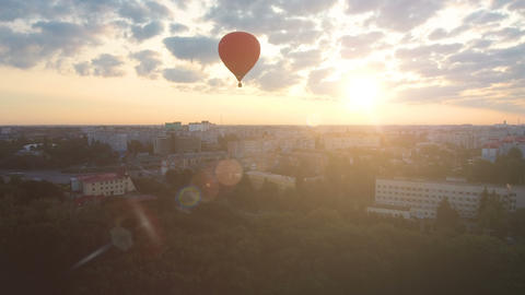 Sun rising on horizon, red hot air balloon floating over city, cherished dreams Footage