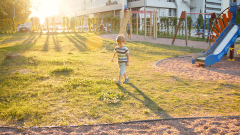 4k footage of cute toddler boy running on playground in park at sunset Footage