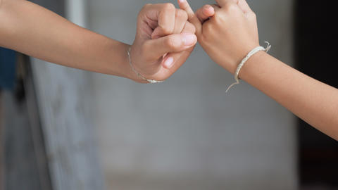 Hand of girl and young woman be hand in hand metaphor contact commitment and Live Action