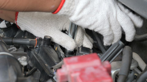 Hands of mechanic man using fix wrench to loosen car spark plug socket Live Action