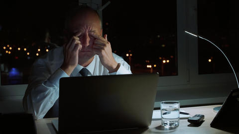 Tired businessman rubbing eyes while executive working by notebook in night Footage