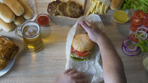 Fat man's hands unpacking fresh burger and carrying it to his mouth, greasy food Live Action