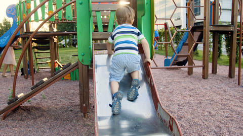 4k video of little toddler boy climbing on metal slide on playground at park Footage