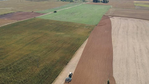 Tractor cultivating harvested crop rapeseed field, aerial view Archivo