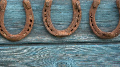 Three lucky old rusty horseshoe on wooden wall Footage