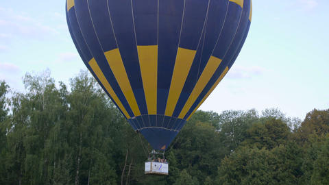 Leisure tour, hot air balloon with passengers flying over the ground, recreation Footage