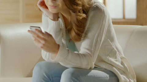 Female sitting on couch and viewing photos in social media on smartphone Footage