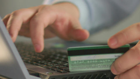 Businessperson typing bank card number on laptop, close-up of man's fingers Live Action