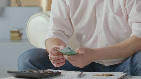Man counting euros, pressing buttons on calculator, making notes, financing Live Action