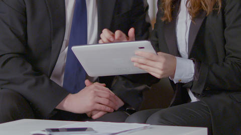 Female assistant showing tablet to director, meeting list and daily schedule Footage