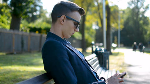 Young successful businessman in a suit and sunglasses is texting, writing a Footage