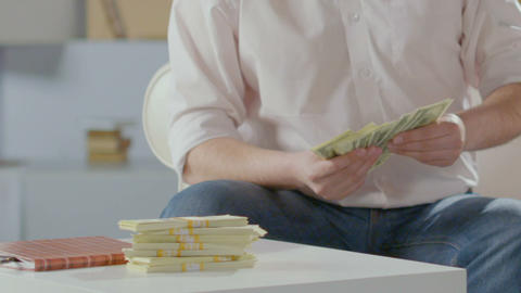 Rich man counting dollars in hands, putting them on table next to wads, wealth Live Action