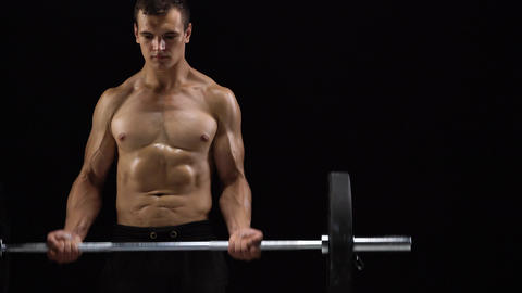 Man is doing exercises with a barbell, training on a black background in the Footage
