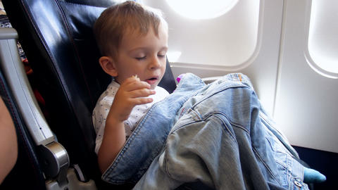 4k video of 2 years old toddler boy eating in airplane during flight Archivo