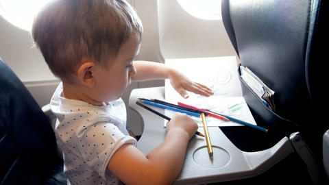 4k footage of little toddler boy drawing with colorful pencil on folding table Footage